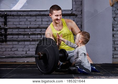 Young sporty father and little cute son sitting near barbell against brick wall in the cross fit gym. Father and son in the sportwear and sportive shoes. Happy family. Rearing children in the healthy lifestyle.