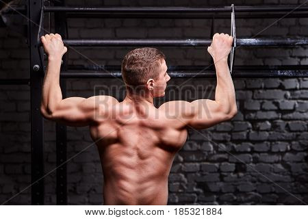 Rear view photo of the young muscular male doing exercises on horizontal bar against brick wall at the cross fit gym. Sportsman withot a shirt. Power and energy, body and muscle. Healthy lifestyle.