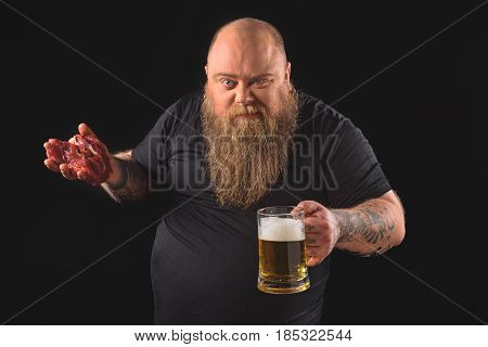 Raw meat is the best snack to beer. Confident fat man is holding glass of beer and looking at camera with aggression. Isolated