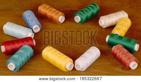 Sewing thread spools of different colors. Sewing tools frame