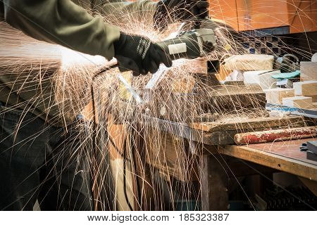 Man Working With Electric Grinder Tool On Steel