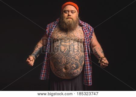 Portrait of confident fat man showing his large belly with tattoo. He is standing and looking at camera with seriousness. Isolated on black background
