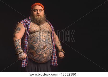 Serious thick male hipster is standing with big tattooed bare abdomen. Isolated and copy space in right side. Portrait
