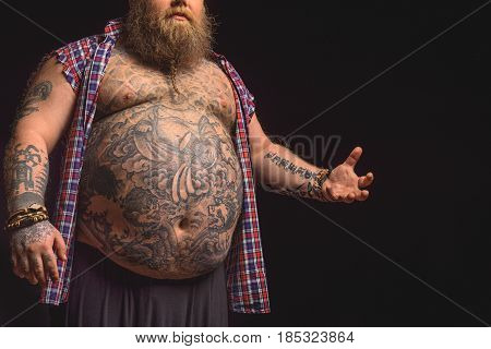 Fat man is standing and gesturing by her arm emotionally. Focus on his naked large belly with tattoos. Isolated and copy space in right side