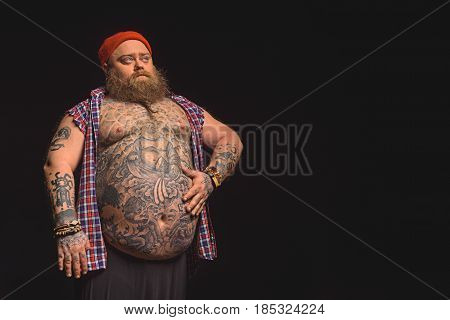Portrait of confident thick male hipster touching his large belly with proud. He is standing and looking forward seriously. Isolated and copy space in right side