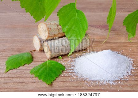 sugar substitute xylitol heap of birch sugar liefs and wood on wooden background