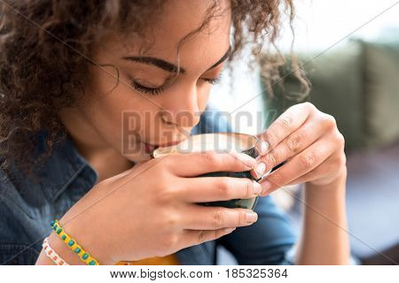 This is very appetizing. Focus on close up face of african woman tasting delicious coffee in cafe