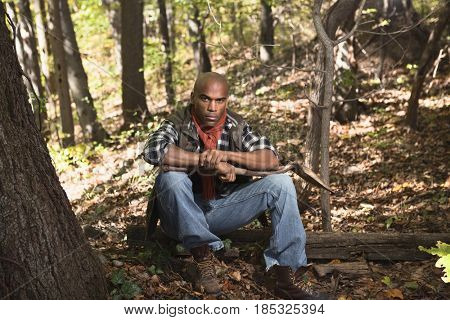 African American man sitting in woods