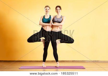Photo of young sportswomen practicing yoga in sportswear
