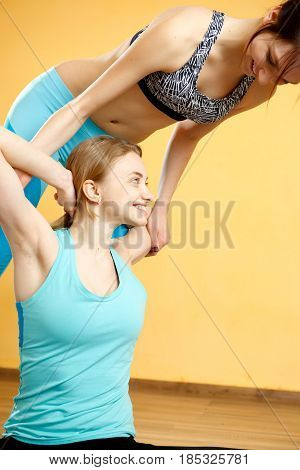 Beautiful sportswomen doing stretching exercises in gym