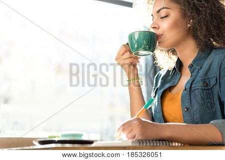 This delicious smell. side view female expressing gladness while tasting mug of beverage