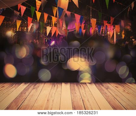 Night party decoration background wooden floor and colorful flags over bokeh vintage filter effect.