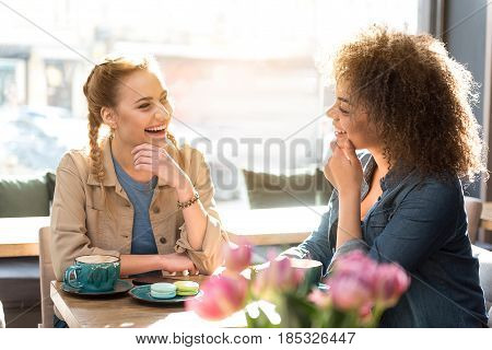smiling mulatto woman telling with outgoing caucasian girl. They sitting at table in confectionary shop