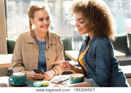 Happy female making conversation with laughing friend while situating at desk in cafe