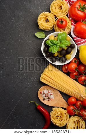Pasta, vegetables, herbs and spices for Italian food on black background, top view, copy space