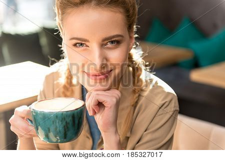Portrait of woman expressing thoughtfulness while drinking cup of coffee in confectionary shop