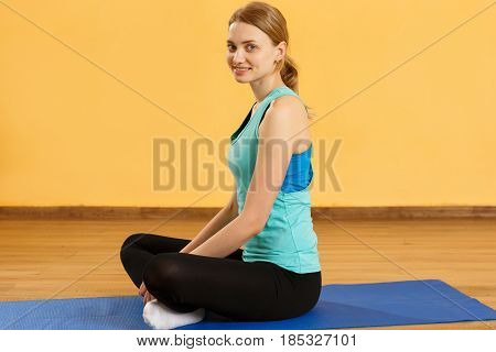 Young girl in lotus pose on rug at gym