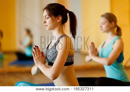 Young girls in lotus pose on rug at gym