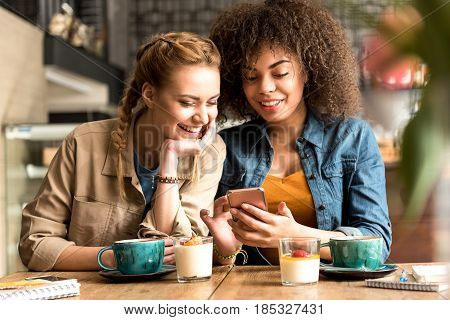 Outgoing girl speaking with cheerful african friend while sitting at table in confectionary shop. They looking at mobile