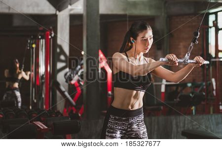 Athletic young woman executed exercise with exercise-machine Cable Crossover in gym.