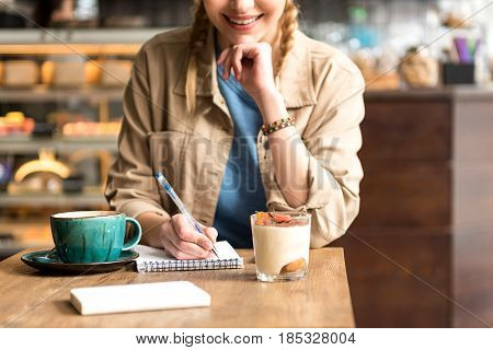 Female demonstrating cheerfulness while writing in copybook in cafe. She drinking coffee and eating dessert at table