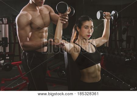 Athletic young woman lifting weights with help from instructor and fitness trainer in gym.