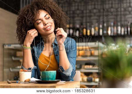 Woman expressing pleasure while hearing song in confectionary shop. She sitting at desk