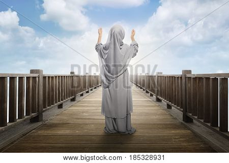Back view of asian muslim girl standing and praying to god with blue sky background
