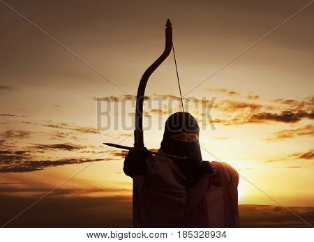 Asian Muslim Woman Wearing Hijab Holding Bow To Shoot An Arrow