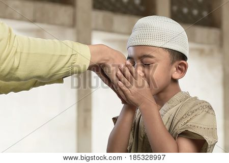 Asian Muslim Child Kissing A Hand From An Old People