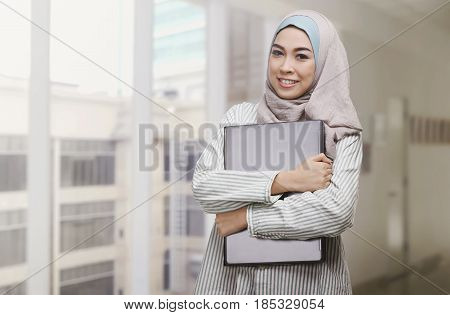 Beautiful Asian Muslim Woman Holding Laptop
