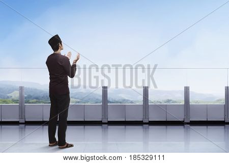 Young Asian Muslim Man Praying With Raising Hand In The Balcony
