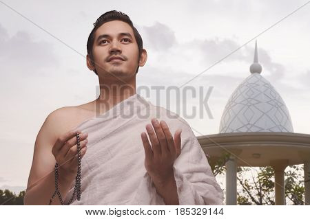 Smiling Asian Muslim Man With Ihram Clothes Holding Prayer Beads