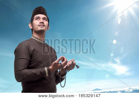 Young Asian Muslim Man With Prayer Beads Pray To God