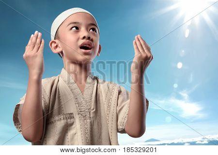 Cheerful Asian Muslim Child In Traditional Dress Praying