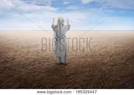 Back View Of Asian Muslim Kid In Traditional Dress Praying To God