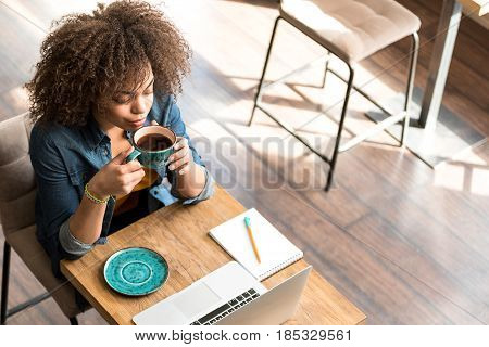 Top view of calm female drinking mug of delicious beverage while locating at table in confectionary shop