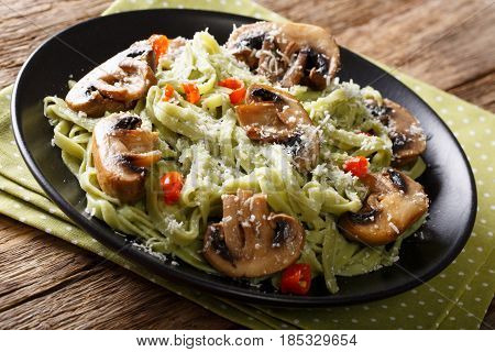 Delicious Spinach Pasta With Fried Mushrooms, Pepper And Cheese Close-up On A Plate. Horizontal