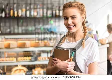 Portrait of woman expressing happiness while working in confectionary shop. She keeping copybook in hands