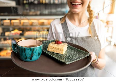 Focus on close up piece of pie and mug of coffee locating on salver. Beaming female keeping it in hand