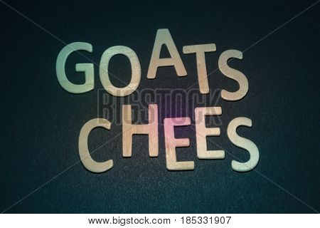 Goats Chees written with colorful wooden letters on a blue background to understand the concept of nutrition and advertising