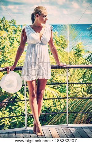 Beautiful woman in the beach house, standing on the balcony and enjoying bright sunny day, happy summer vacation on the tropical resort