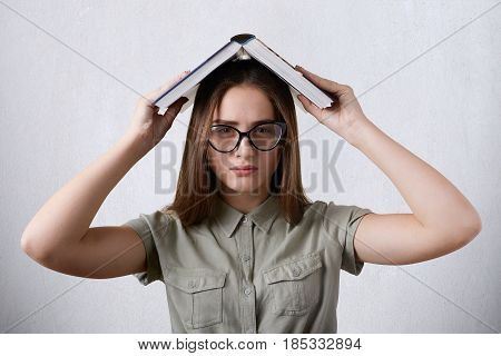 A Horizontal Portrait Of Young Female Student Wearing Eyeglasses And Shirt Holding Book On Head Bein