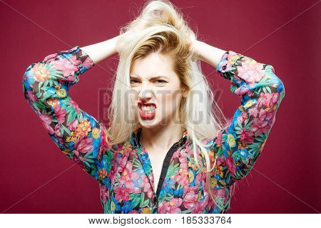 Portrait of Aggresive Woman on Pink Background. Emotional Girl with Long Hair in Colorful Shirt is Looking at the Camera in Studio.