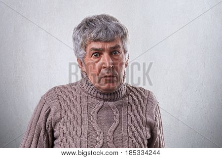 A Portrait Of Astonished Mature Man With Gray Hair Wearing Sweater Looking With Wide Open Eyes Into