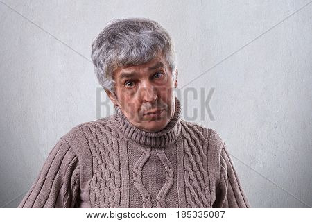 An Old Male With Wrinkles Having Gray Hair Dressed In Sweater Having Sympathetic Expression Isolated