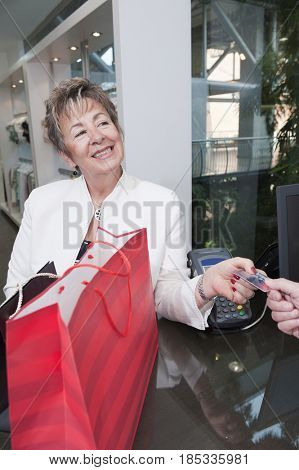 Senior Hispanic woman paying with credit card
