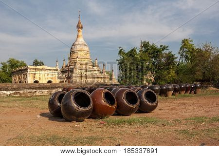 Big ceramic pots have lying  on the sunny square in the front of the buddhist stupa