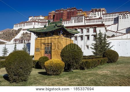 A small yellow pavilion with a green roof and a decorative bush in front of the Potala Palace in Lhasa