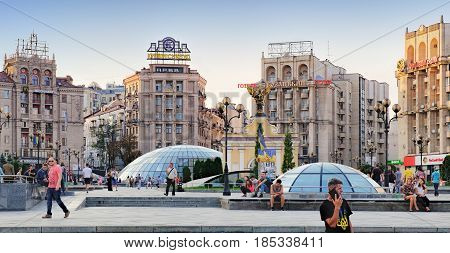 Kiev, Ukraine - September 11, 2016: Independence Square at weekend. People walking through square passing cafes restaurant and shops. Man in t-shirt with emblem of Ukraine stands in the foreground